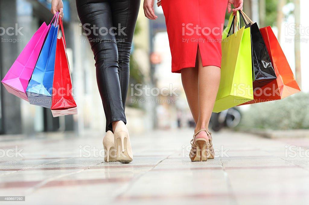 Two fashion women legs walking with shopping bags stock photo