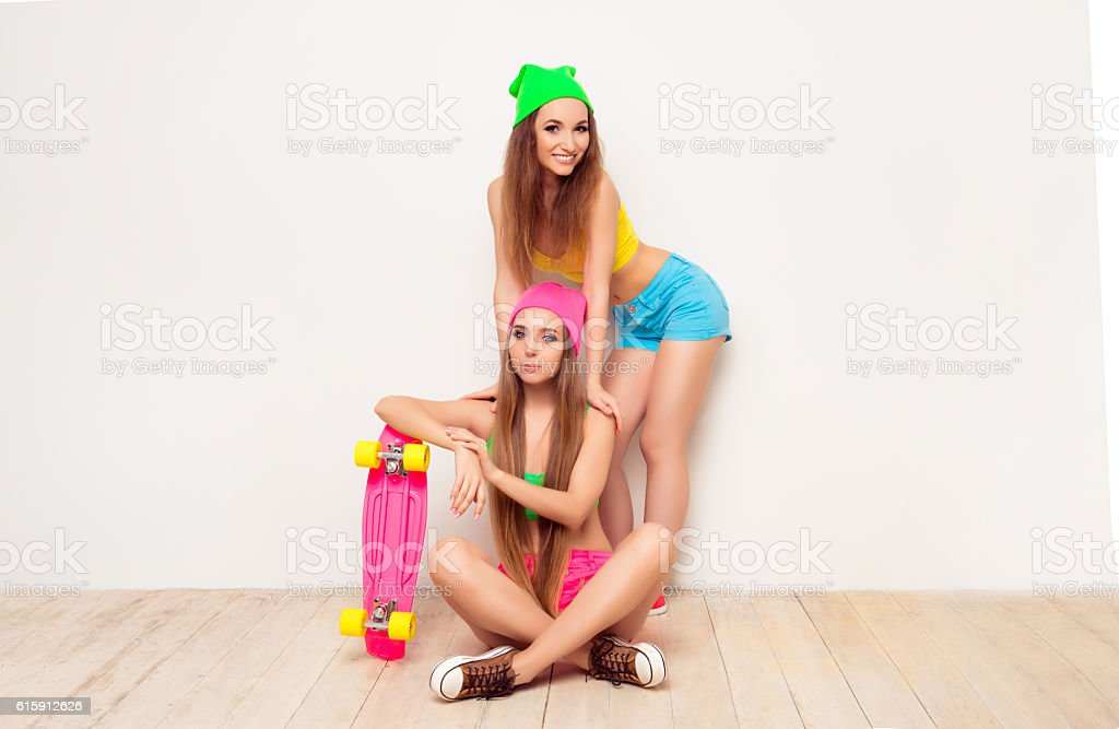 Two fashionable pretty girls with skateboard on white background stock photo
