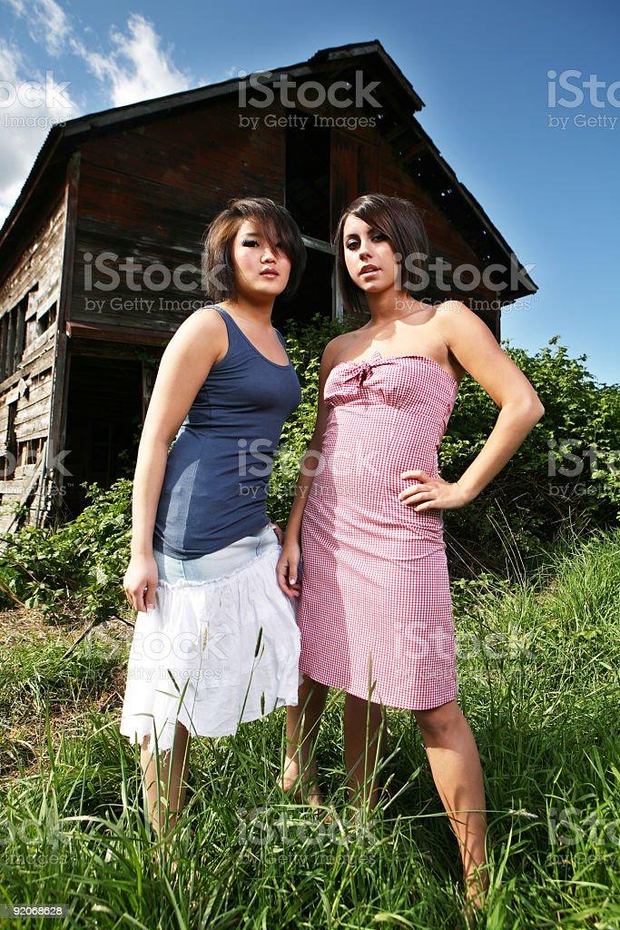 Two Fashionable Women Outside Abandoned Barn royalty-free stock photo
