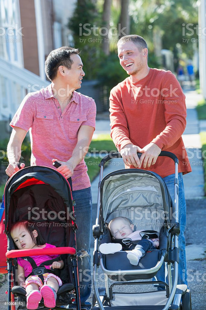 Two fathers pushing strollers, laughing, talking stock photo