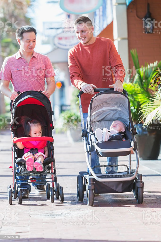 Two fathers pushing strollers, talking stock photo