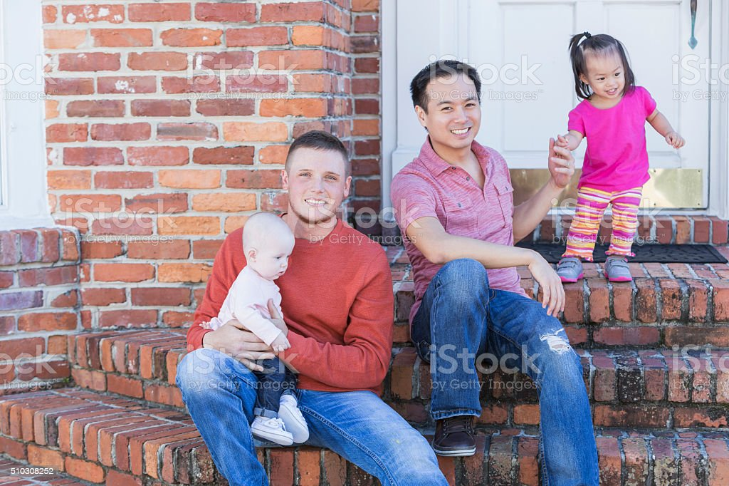 Two fathers with their young children sitting on steps stock photo