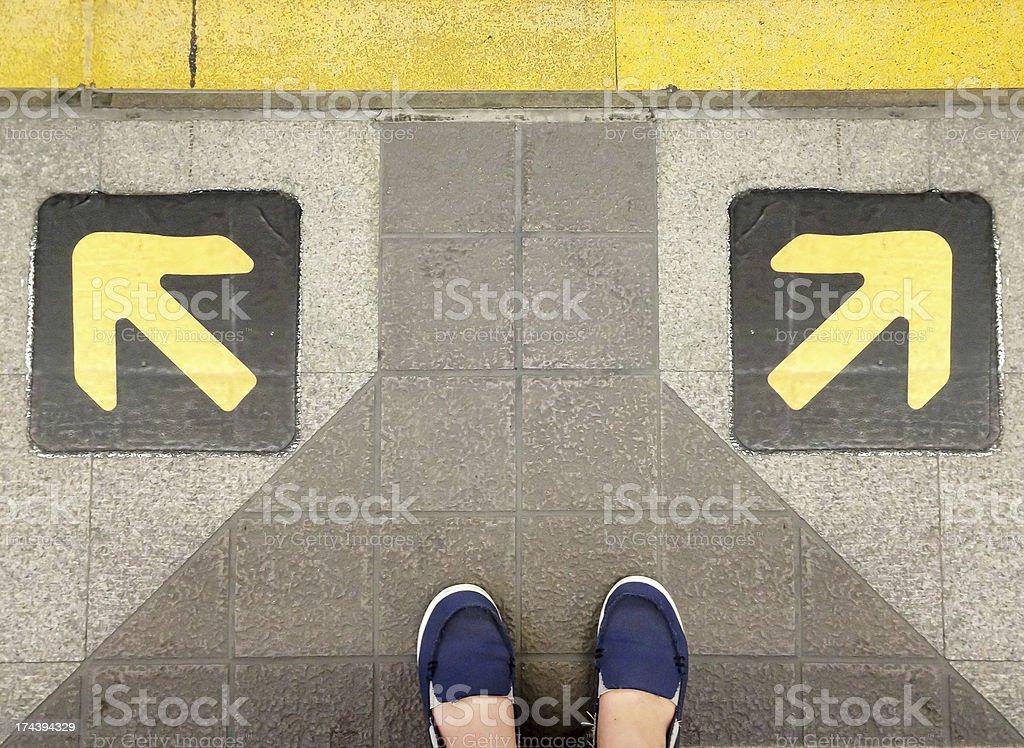 Две ноги на стрелки в противоположных направлениях Стоковые фото Стоковая фотография