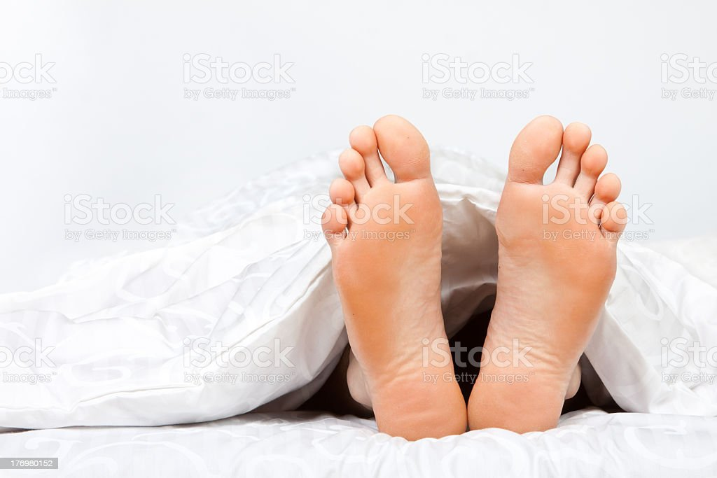 Two feet poking out from under a duvet stock photo