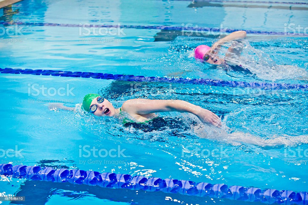 Two female athletes swimming in indoor pool stock photo