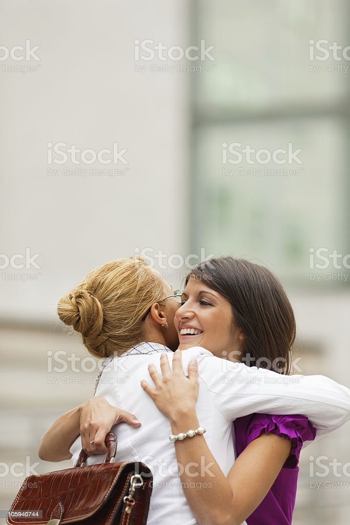 Two female colleagues embracing each other royalty-free stock photo