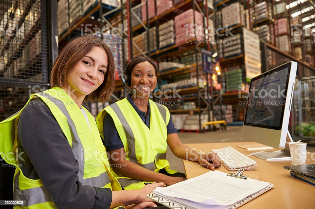 Two female colleagues in a warehouse office look to camera stock photo