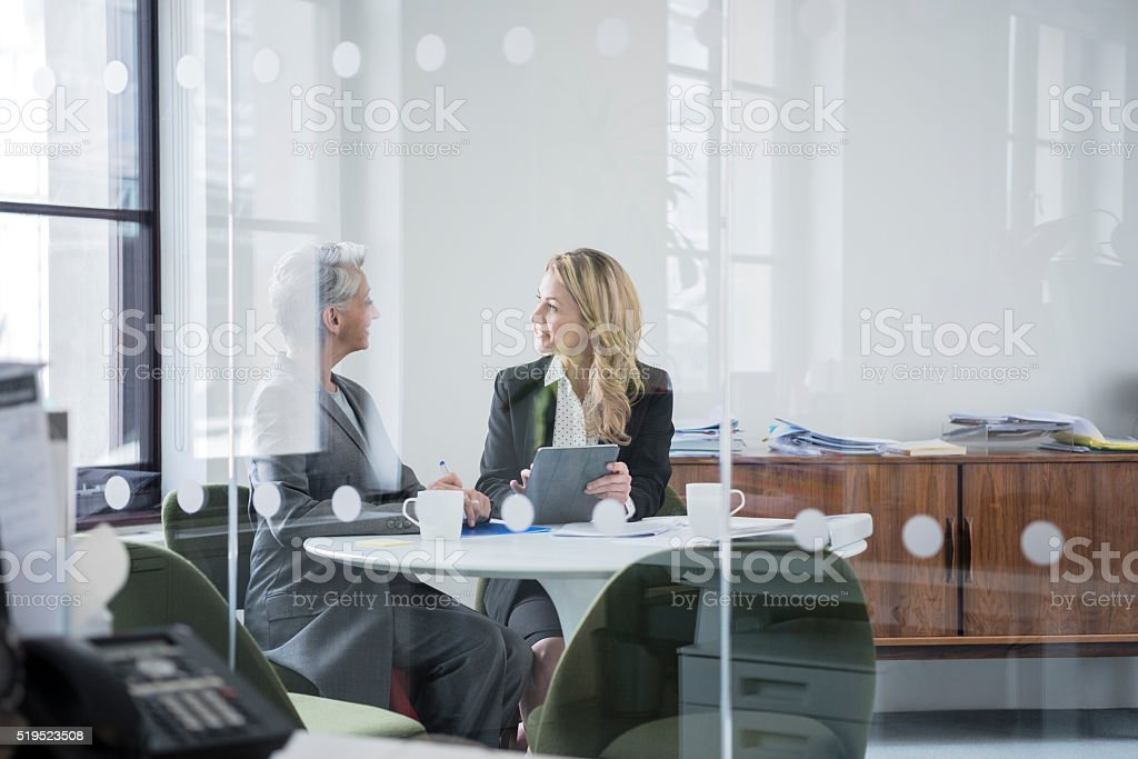 Two female colleagues sitting behind glass partition in modern office stock photo