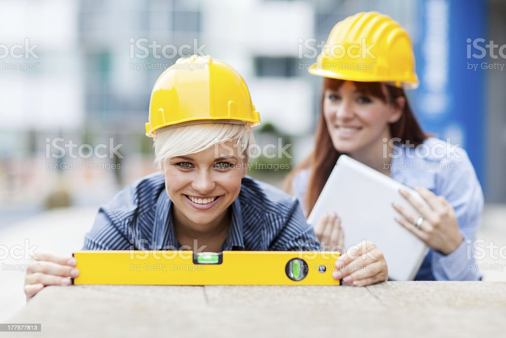Two Female Constructors are working with a level royalty-free stock photo
