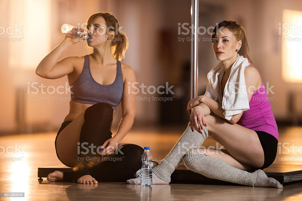 Two female dancers taking a break from pole dancing. stock photo