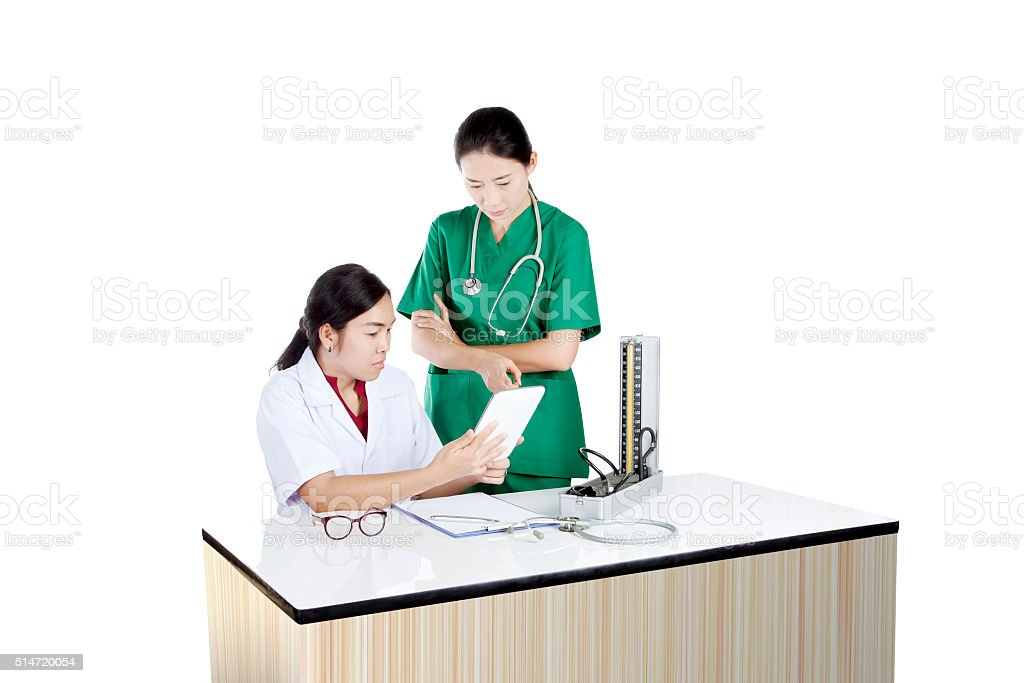 two female doctor using tablet computer reviewing medical char stock photo