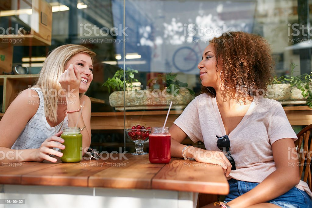 Two female friend having a chat in cafe stock photo