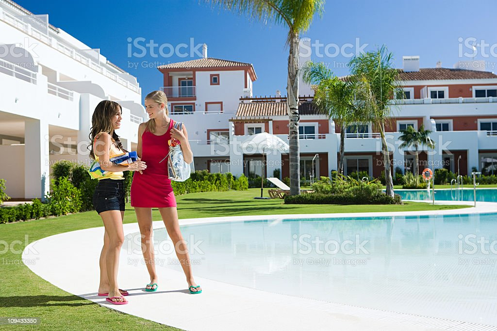 Two female friends by poolside on vacation royalty-free stock photo