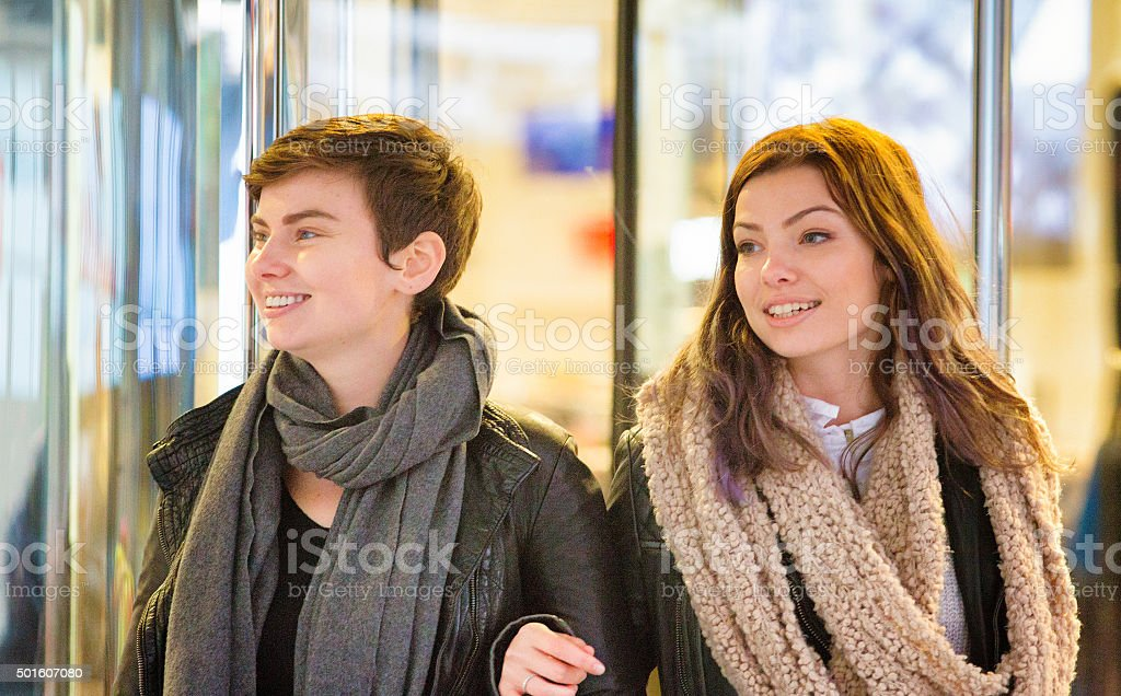 Two female friends come out of store smiling stock photo