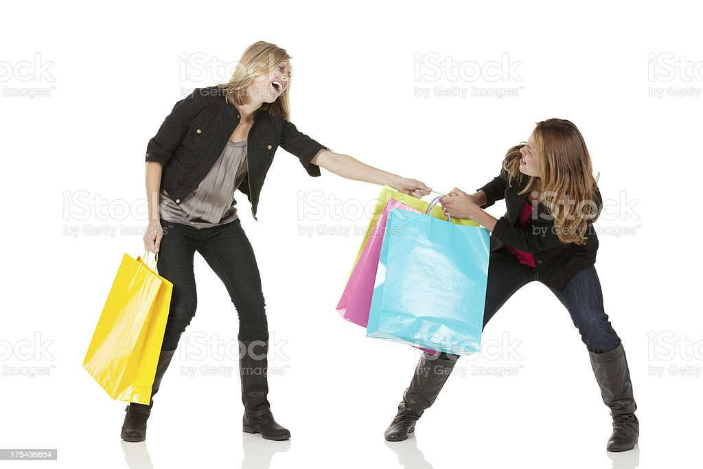 Two female friends fighting for a shopping bag stock photo