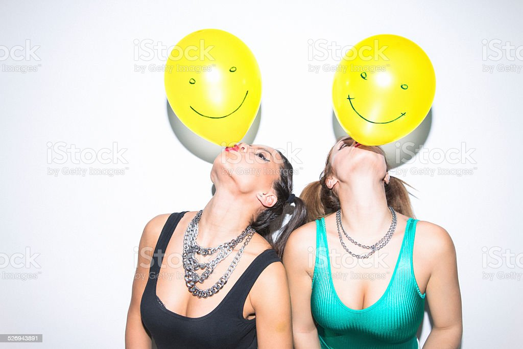 Two female friends having fun blowing up balloons on party stock photo