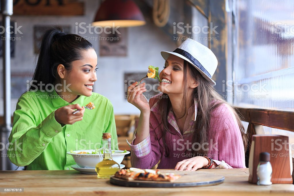 Two female friends having lunch in restaurant stock photo