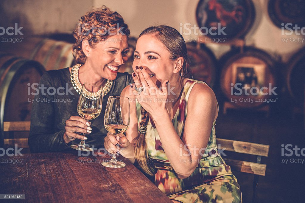 Two Female Friends in Wine Cellar Holding Wineglasses stock photo