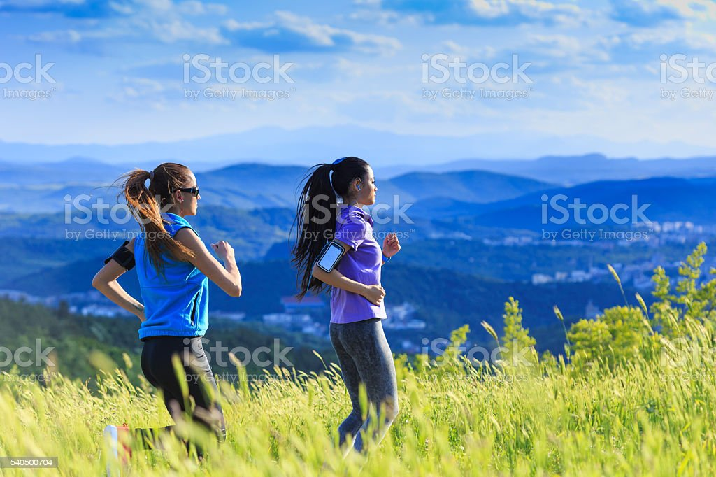 Two female friends jogging in the mountain stock photo