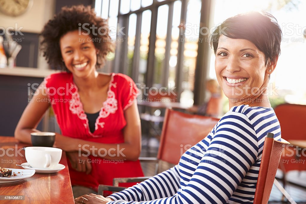 Two female friends meeting at a coffee shop stock photo