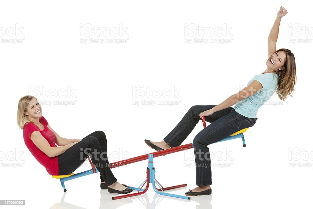 Two female friends playing on a seesaw stock photo