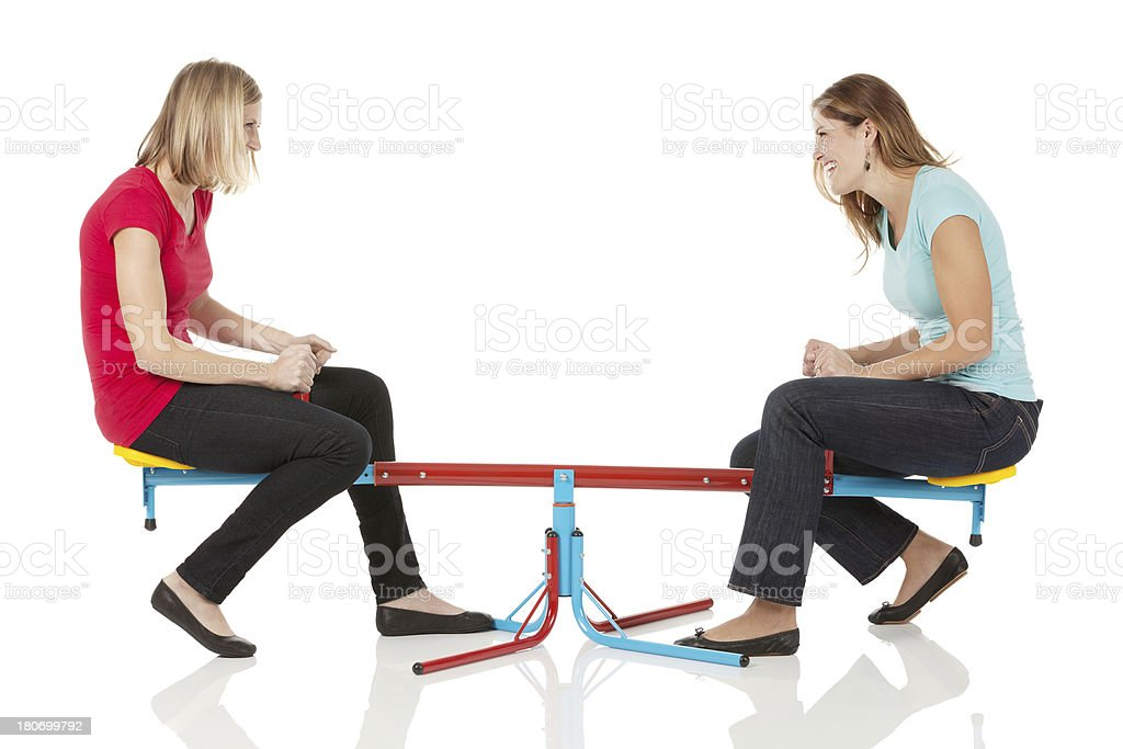 Two female friends playing on a seesaw royalty-free stock photo