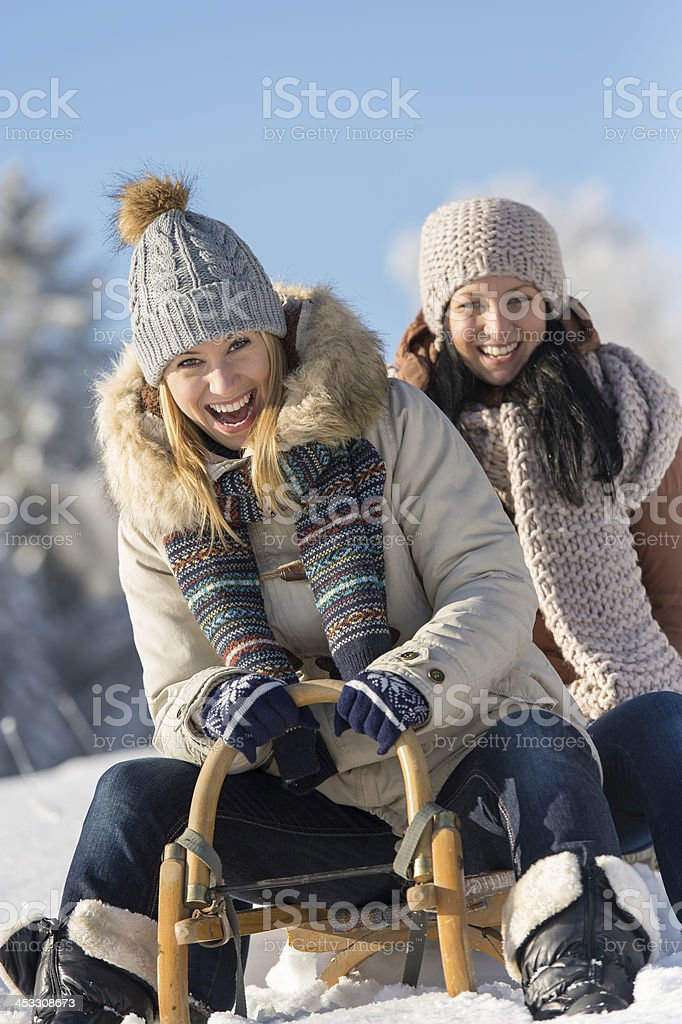 Two female friends sledge downhill in wintertime stock photo