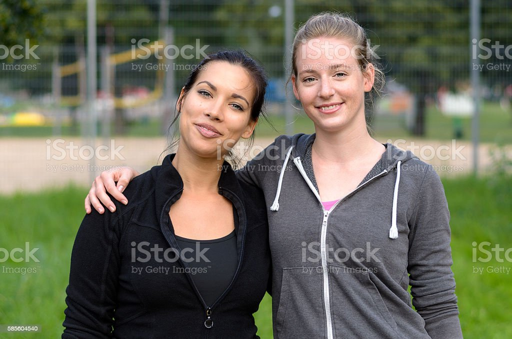 Two female friends standing together stock photo