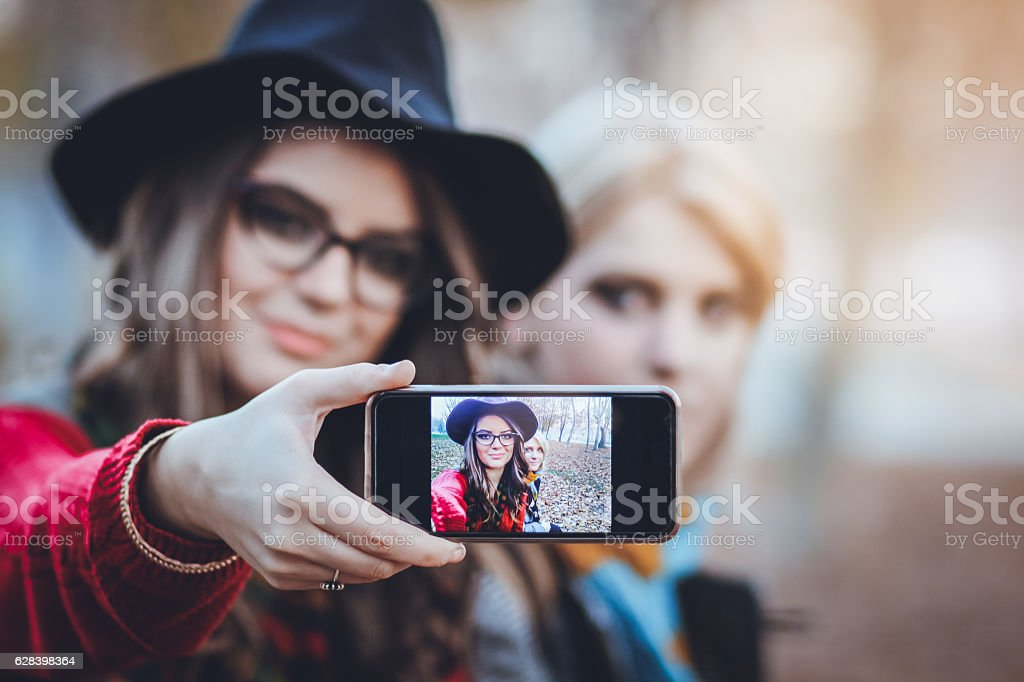 Two female friends taking a selfie with smartphone stock photo