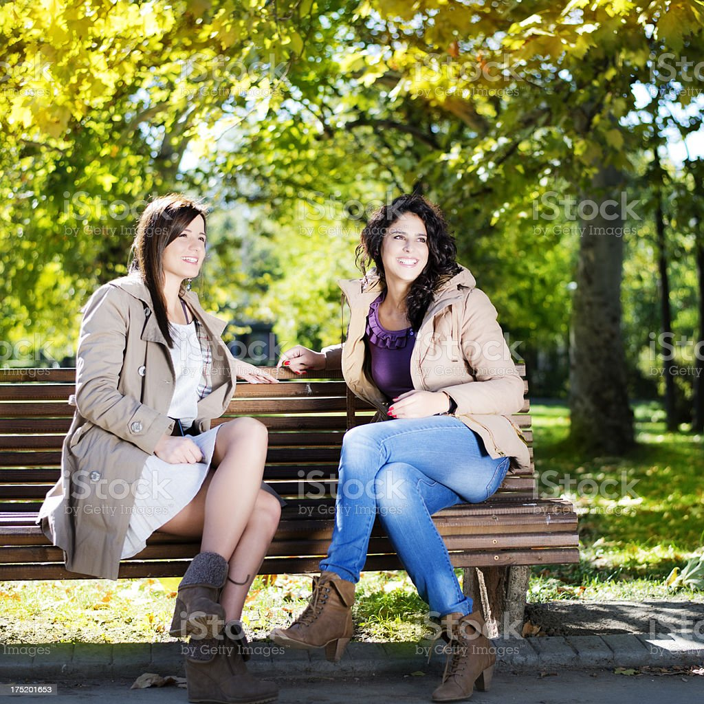 Two female friends talking in a park royalty-free stock photo
