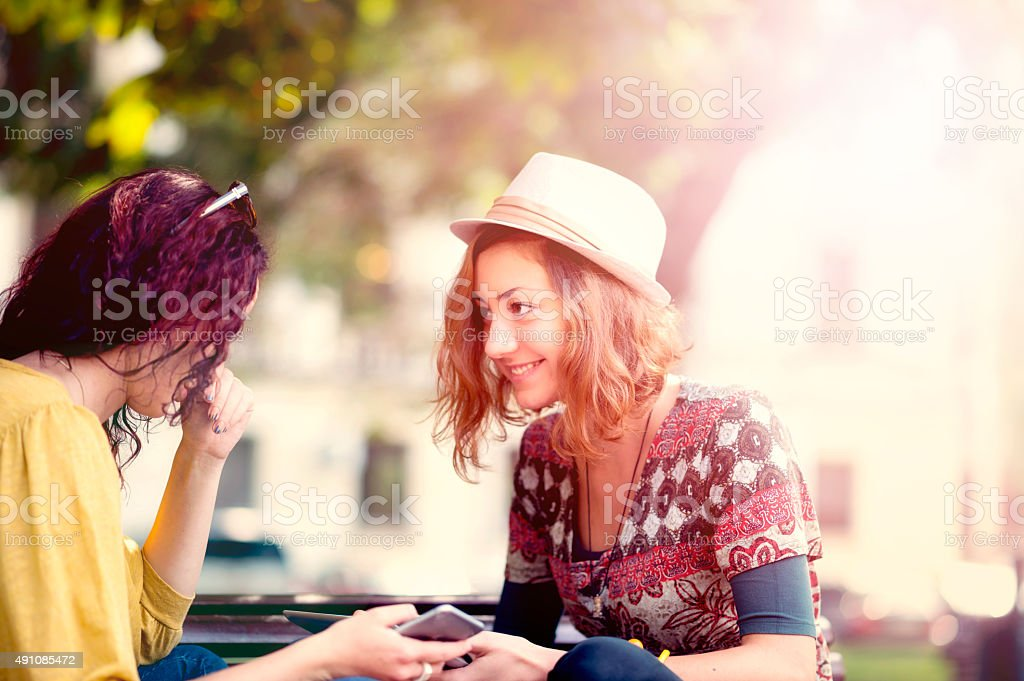 Two female friends talking in a park stock photo