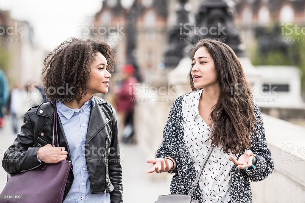 Two female friends talking outdoors in Paris, France stock photo