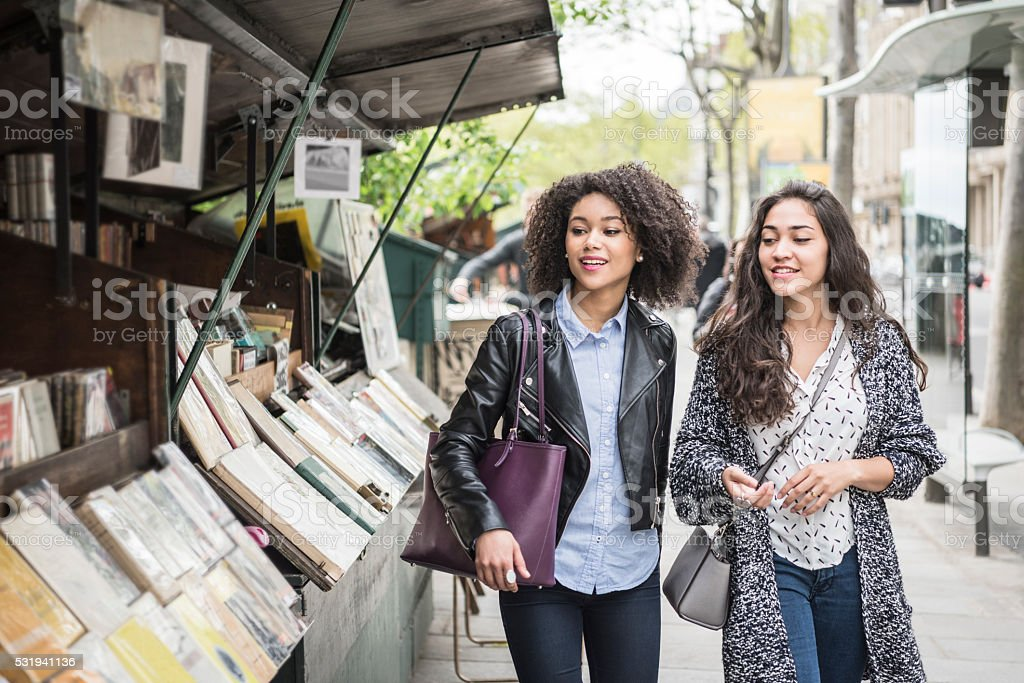 Two female friends walking past bookshop stock photo