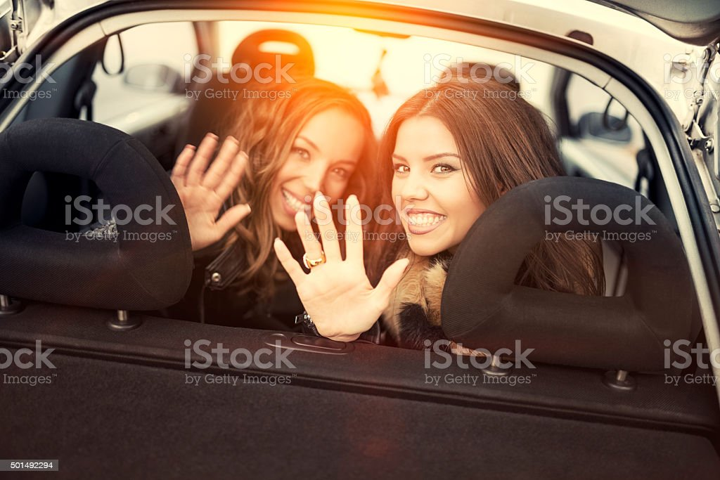 Two Female Friends Waving Goodbye from Back Seat stock photo
