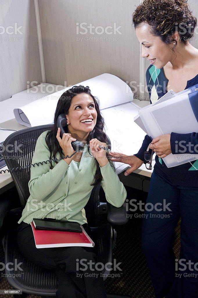 Dos mujeres hispanos los trabajadores de oficina en cubículos foto de stock libre de derechos