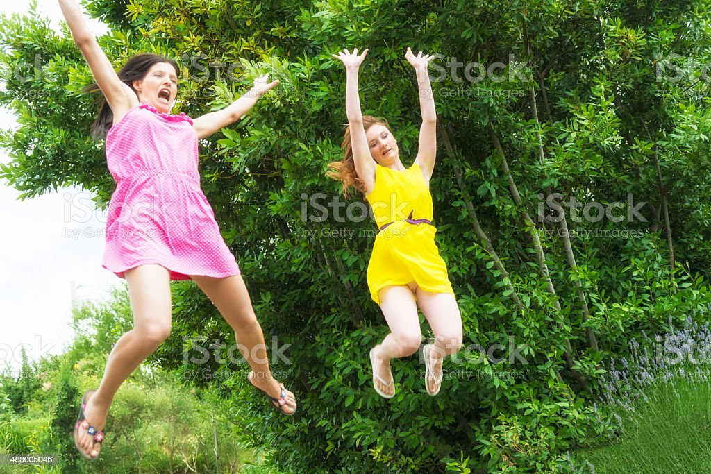 Two female jumping in the air with horror stock photo