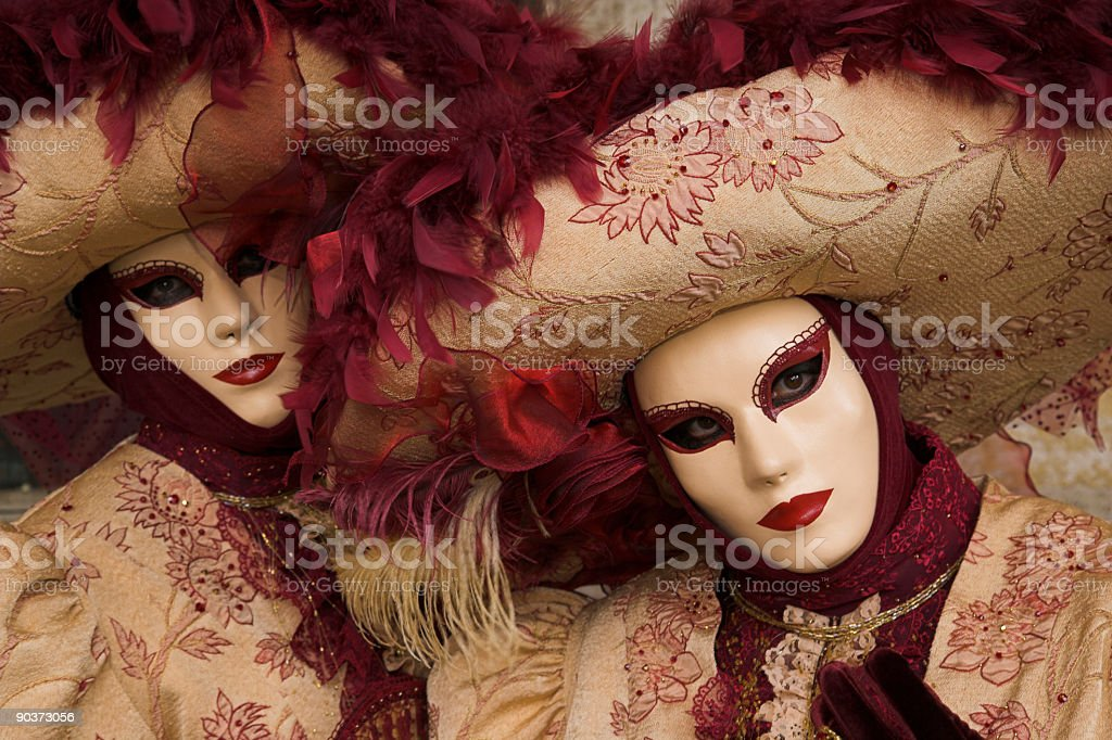 Two female masks with beautiful costumes at carnival in Venice stock photo