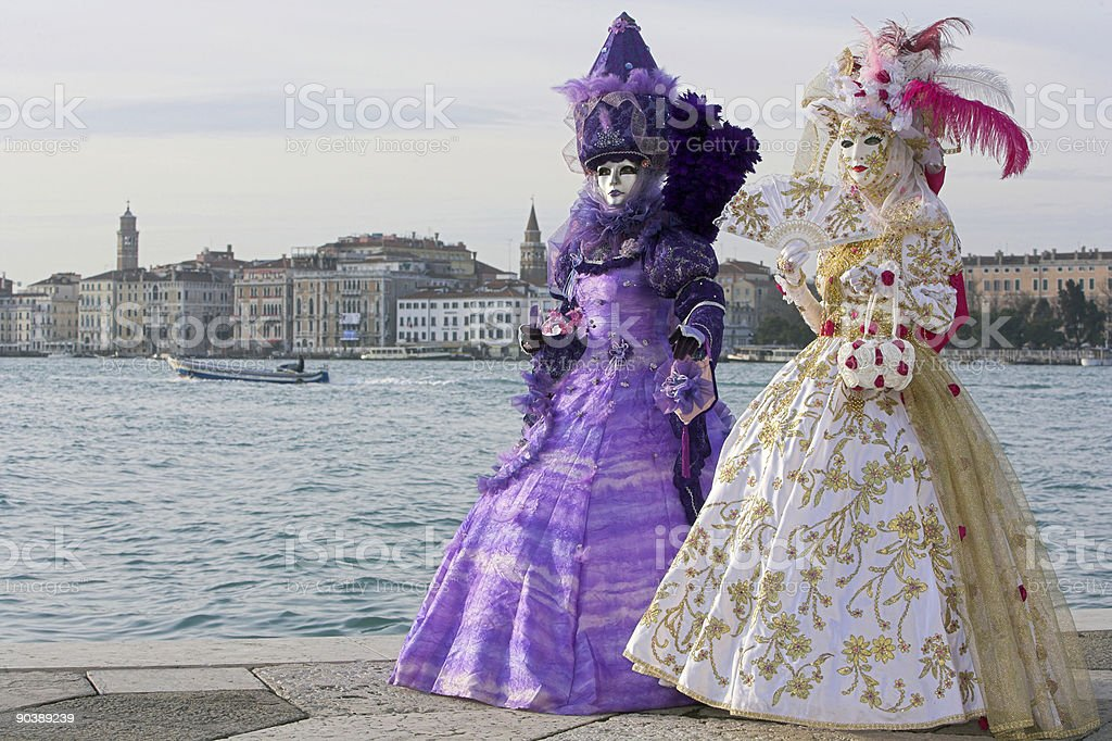 Two female masks with beautiful costumes at Venice skyline (XXL) royalty-free stock photo
