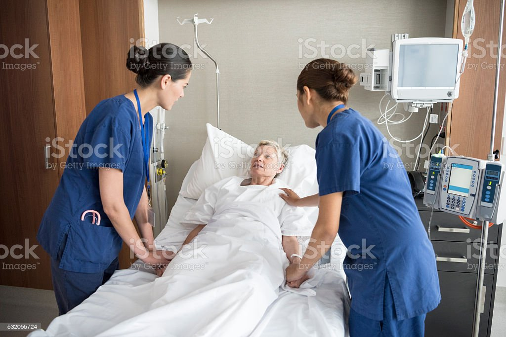 Two female nurses reassuring senior woman in hospital bed stock photo