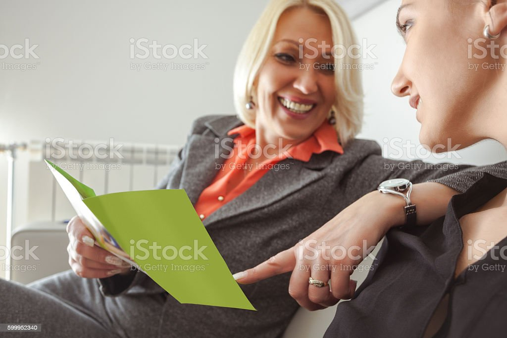 Two female office workers sitting in office, chatting stock photo