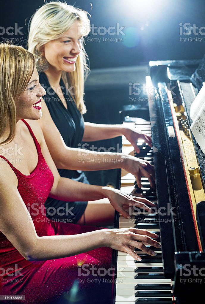 Two female pianists playing the piano. royalty-free stock photo