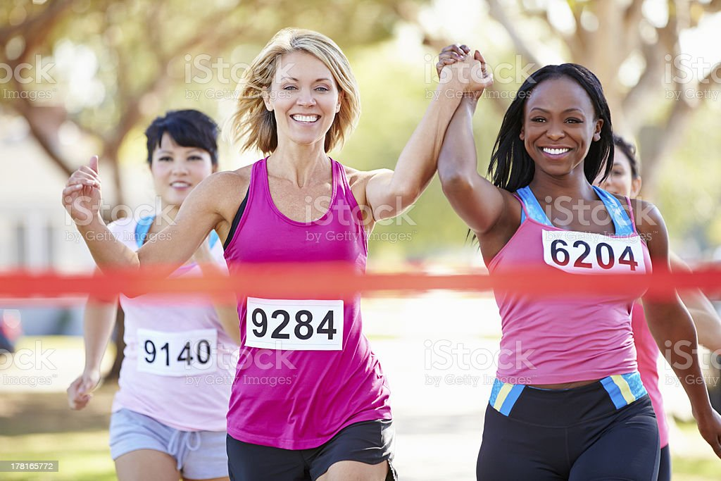 Two Female Runners Finishing Race Together stock photo