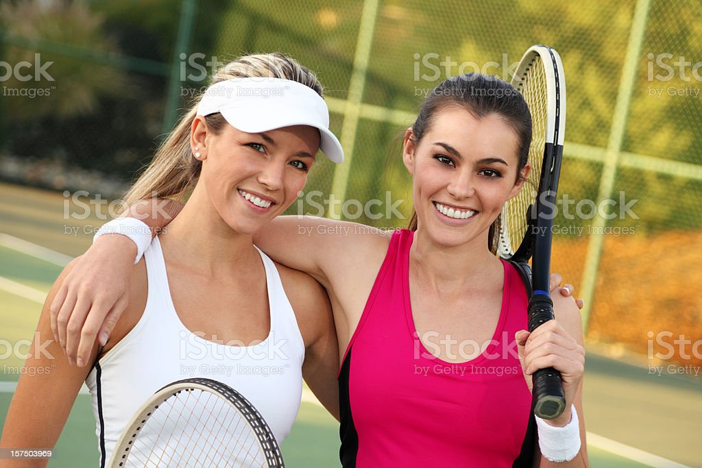 Two female tennis players holding each others' shoulders royalty-free stock photo