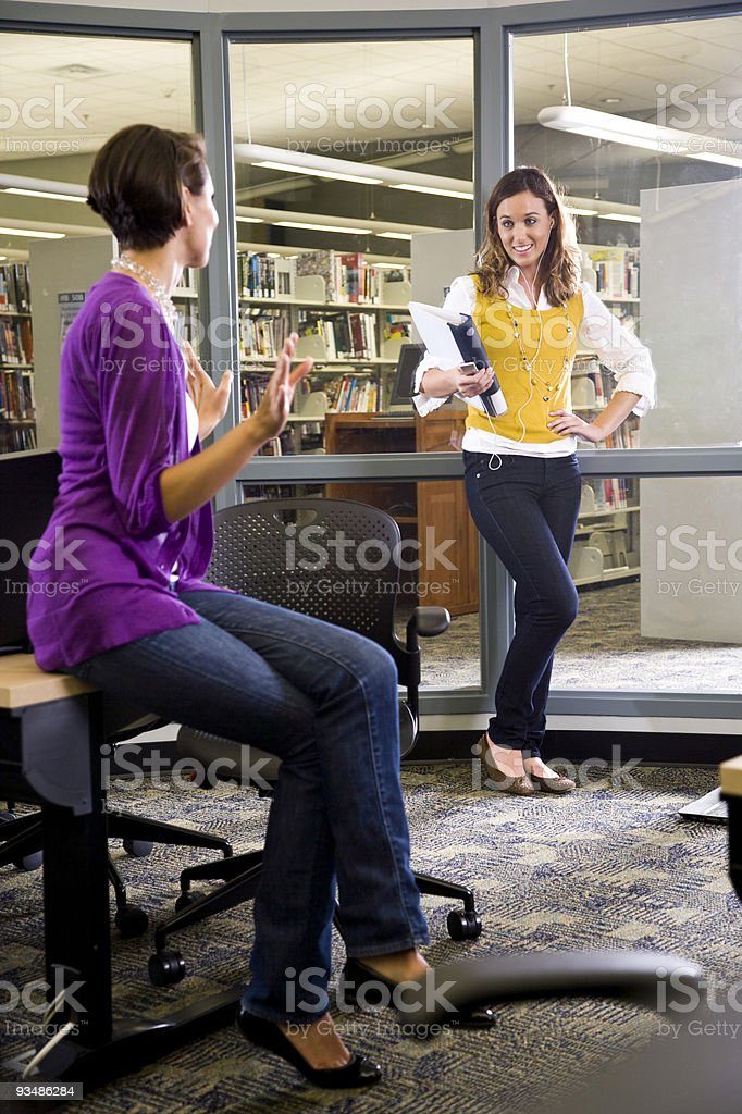 Two female university students conversing in library stock photo