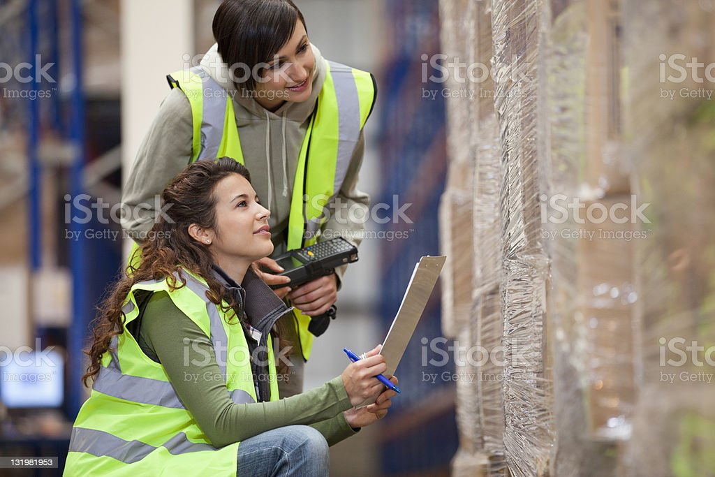 Two female workers with checklist and bar code reader stock photo