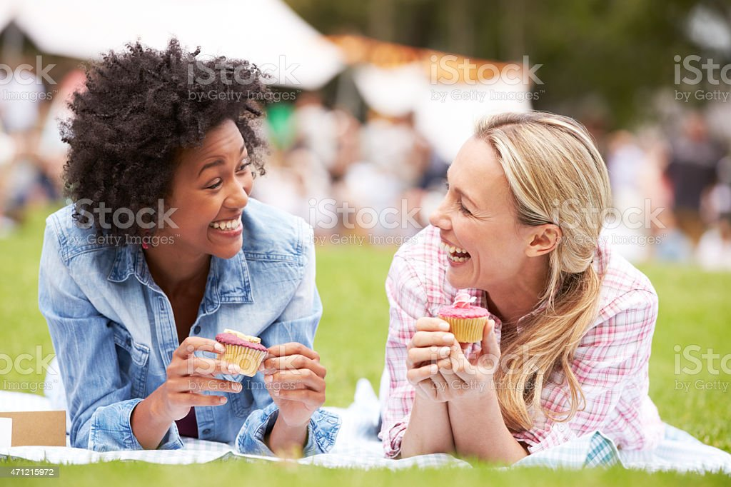 Two females enjoying cupcakes at outdoor summer events stock photo