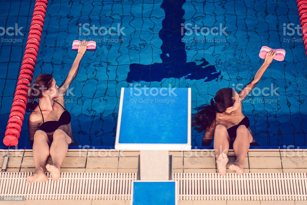 Two Females in Water Aerobics Class at Indoor Swimming Pool stock photo