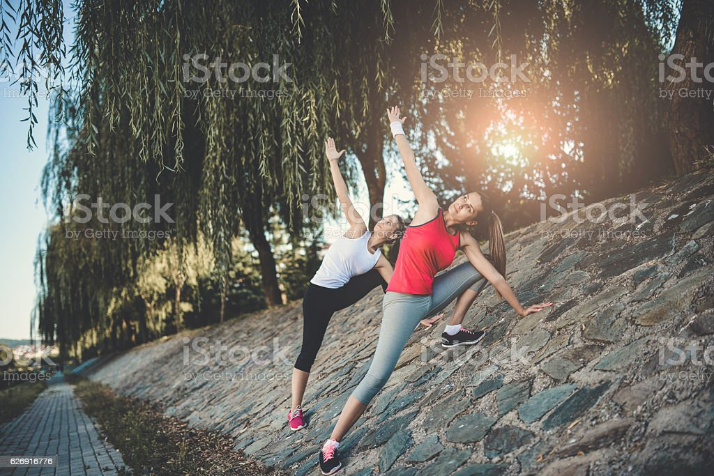 Two Females Practicing Yoga and Stretching Before Jogging in Park stock photo