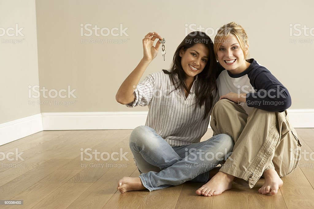 Two females sitting in an empty room holding keys stock photo