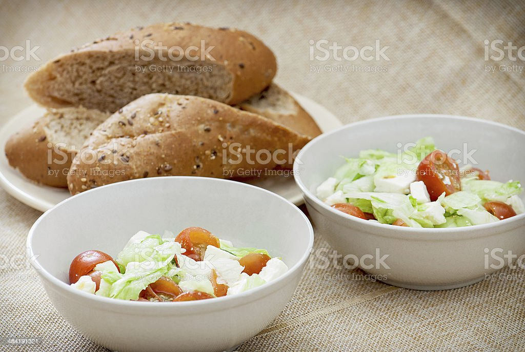 Two fetta salad portions and slices of bread stock photo